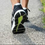 Close-up of Women's running shoes on a paved trail.