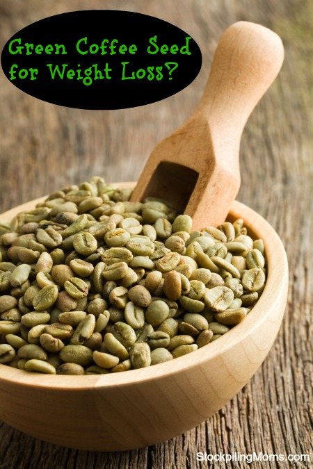 green coffee beans with wooden scoop  in wooden bowl
