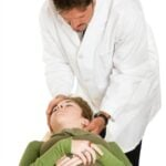 Chiropractor adjusting a young female patient, isolated on white background.
