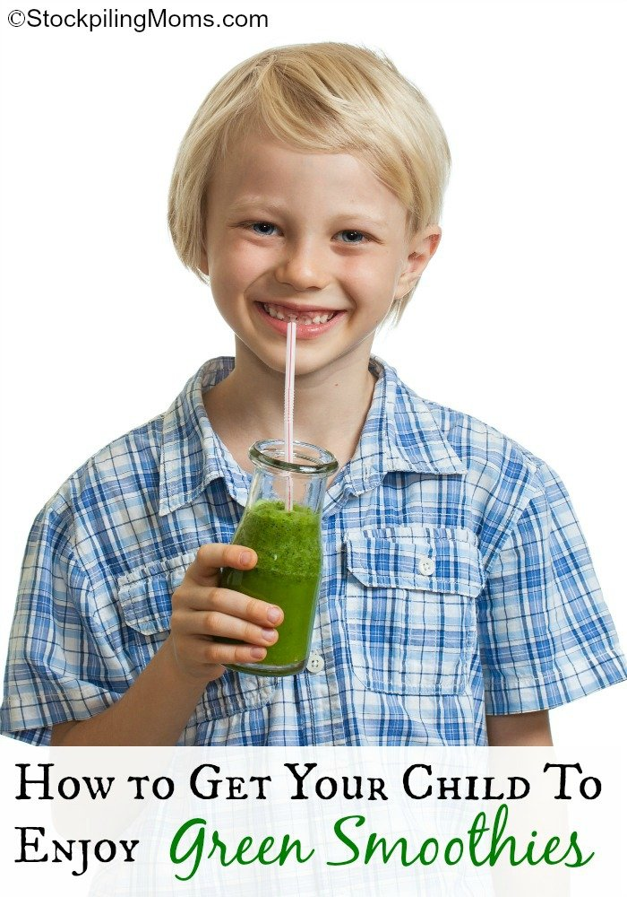 A cute young healthy boy drinking a green smoothie or jucie. Isolated on white.